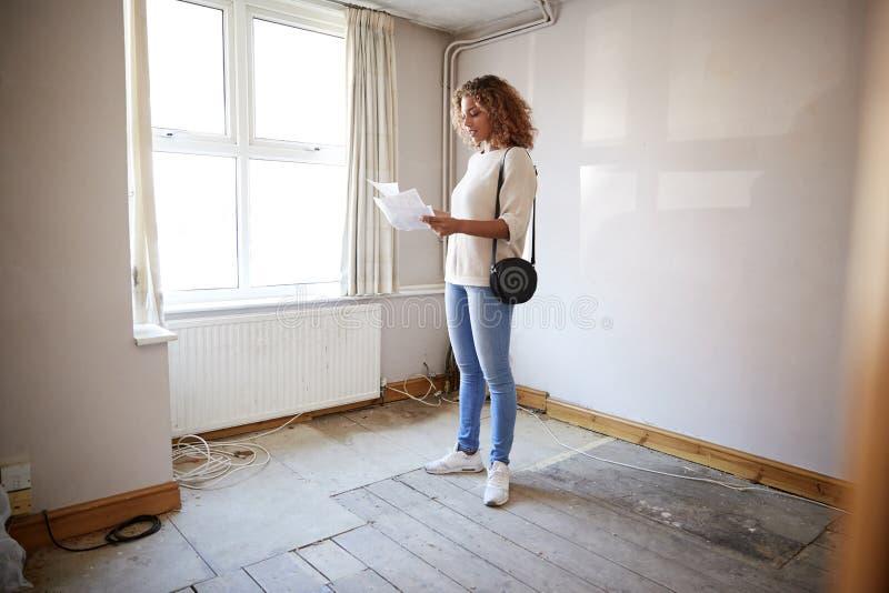 Comprador femenino de la primera vez que mira encuesta sobre la casa en sitio de ser renovado foto de archivo libre de regalías