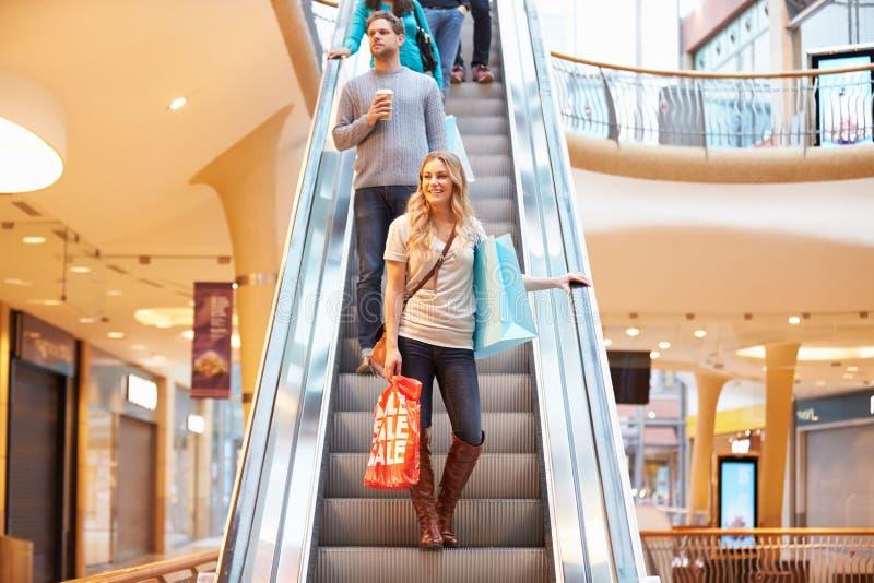 Comprador femenino en la escalera móvil en alameda de compras imagenes de archivo