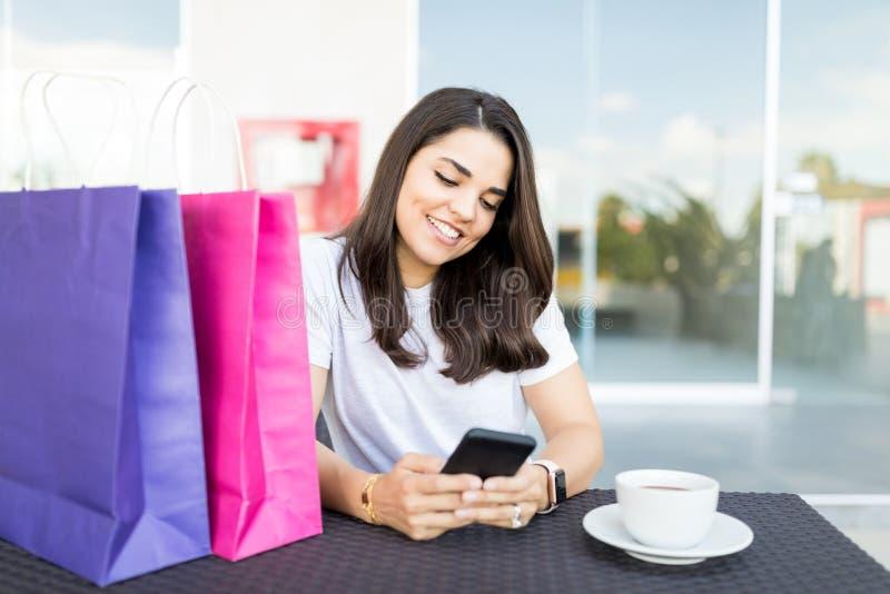 Comprador femenino hermoso que manda un SMS en Smartphone en café fotografía de archivo libre de regalías