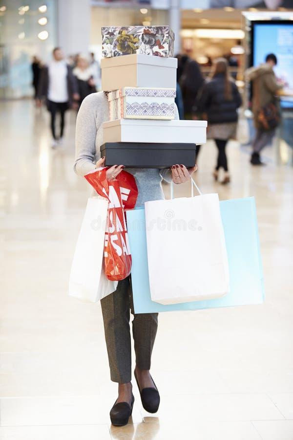 Comprador femenino ocultado detrás de las cajas que hacen compras en alameda imagen de archivo