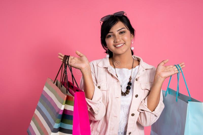 Comprador femenino que sonríe sosteniendo bolsos de compras foto de archivo libre de regalías
