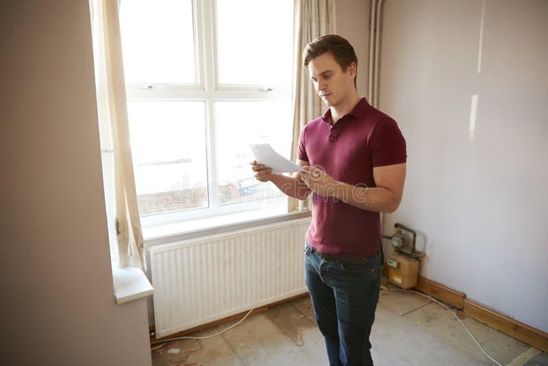 Comprador masculino da primeira vez que olha a avaliação da casa na sala ser renovado foto de stock royalty free