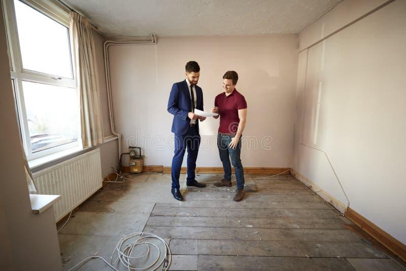 Comprador masculino de la primera vez que mira encuesta sobre la casa con agente inmobiliario imagen de archivo libre de regalías