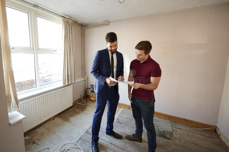 Comprador masculino de la primera vez que mira encuesta sobre la casa con agente inmobiliario fotos de archivo