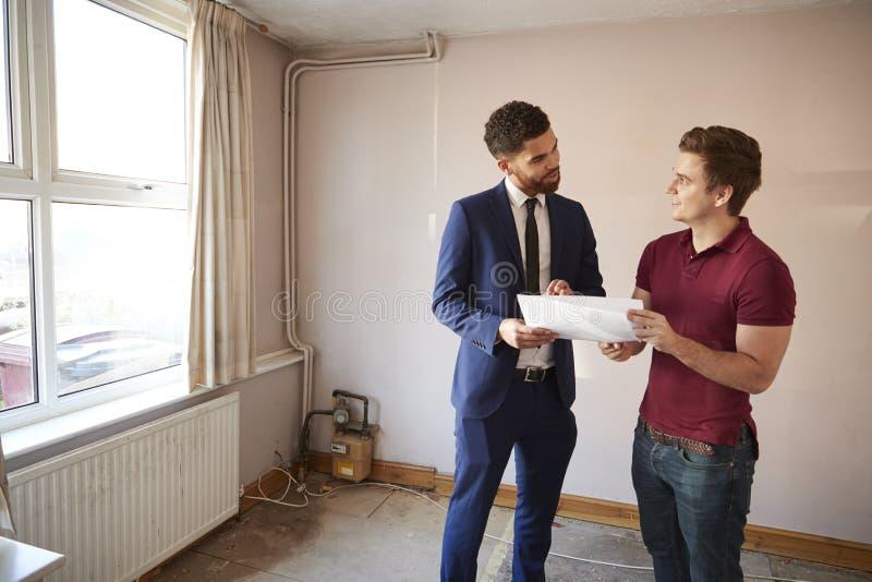 Comprador masculino de la primera vez que mira encuesta sobre la casa con agente inmobiliario imágenes de archivo libres de regalías