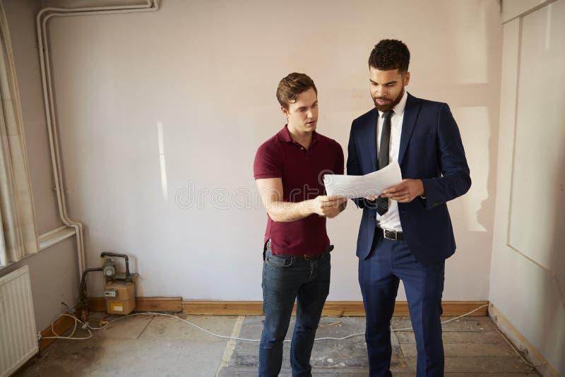 Comprador masculino de la primera vez que mira encuesta sobre la casa con agente inmobiliario fotos de archivo libres de regalías