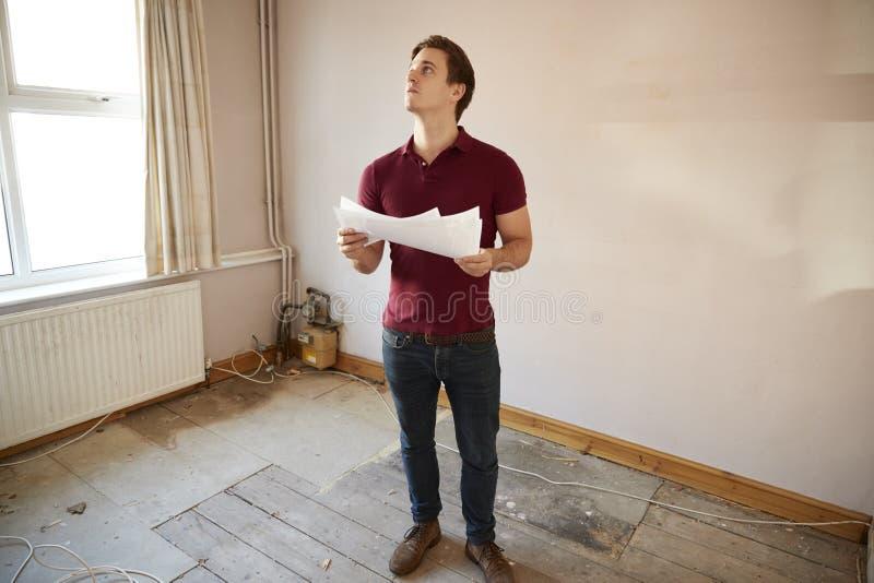 Comprador masculino de la primera vez que mira encuesta sobre la casa en sitio de ser renovado fotografía de archivo libre de regalías