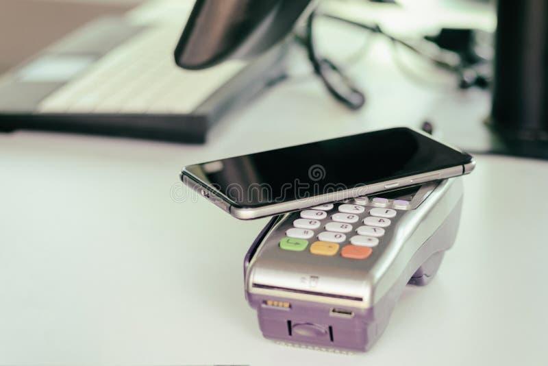 Comprador, pago a través del terminal de la posición teléfono móvil como tarjeta de banco está entonando fotos de archivo libres de regalías