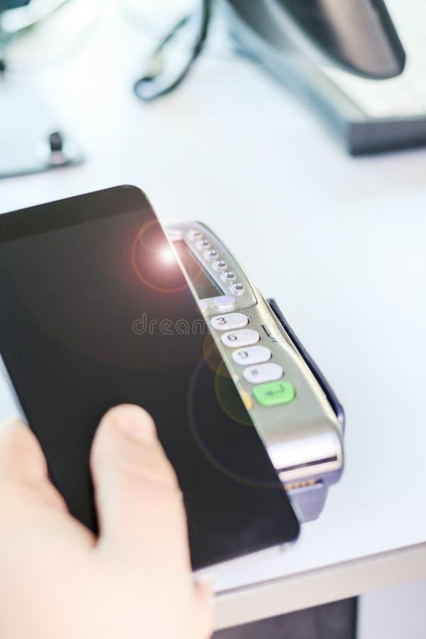 Comprador, pago a través del terminal de la posición teléfono móvil como tarjeta de banco está entonando imágenes de archivo libres de regalías