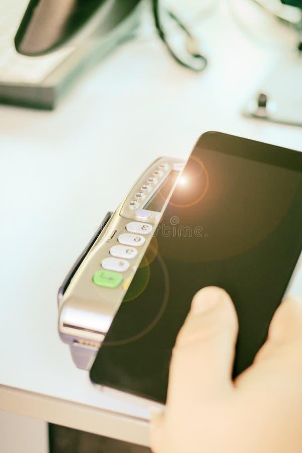 Comprador, pago a través del terminal de la posición teléfono móvil como tarjeta de banco está entonando fotografía de archivo