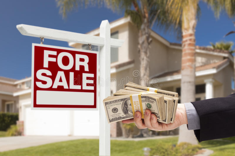 Comprador que cede o dinheiro para a casa com para sinal da venda fotografia de stock royalty free