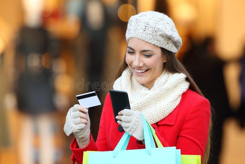 Comprador que paga en línea con el teléfono y la tarjeta de crédito imagen de archivo