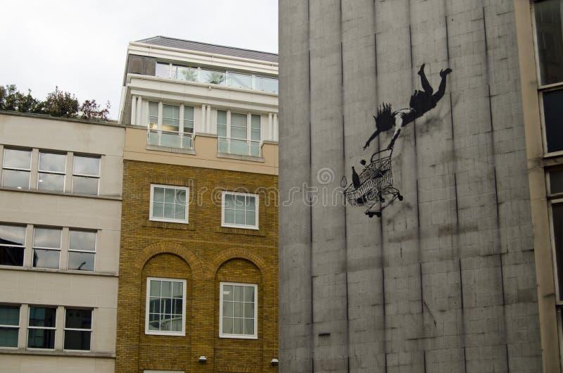 Comprador y carretilla que caen de Banksy fotografía de archivo