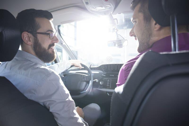 Comprador y distribuidor autorizado sonrientes durante una prueba de conducción en un coche exclusivo imagenes de archivo