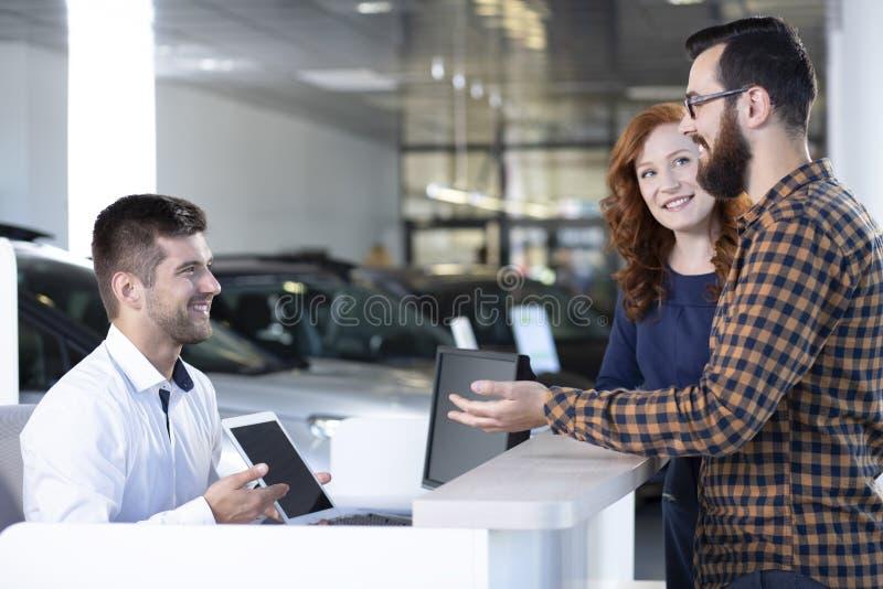 Compradores felizes que falam com o concessionário automóvel com a tabuleta na sala de exposições fotos de stock