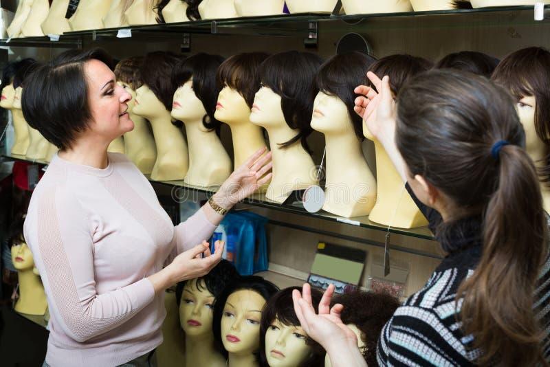 Compradores que discutem sobre o cabelo imagem de stock