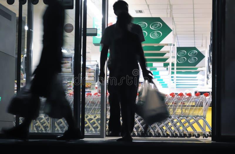 Compradores que salen el colmado (movimiento enmascarado) fotos de archivo libres de regalías