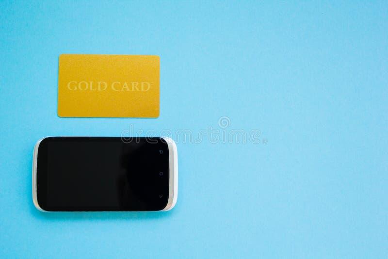 Comprando produtos em linha, pagamento usando um cartão do ouro, conceito de compra em linha, tema azul foto de stock