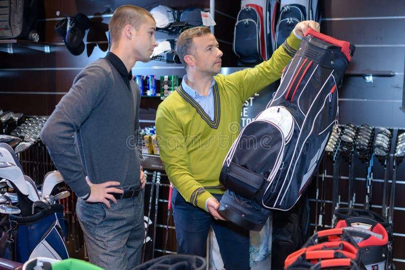 Comprando um saco de golfe imagem de stock royalty free