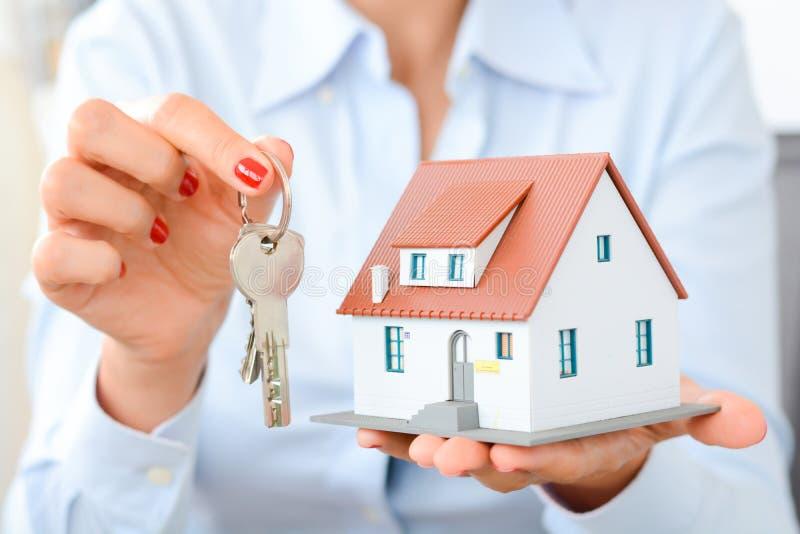 Comprando un concepto de la casa con la mujer da llevar a cabo una casa modelo y llaves foto de archivo