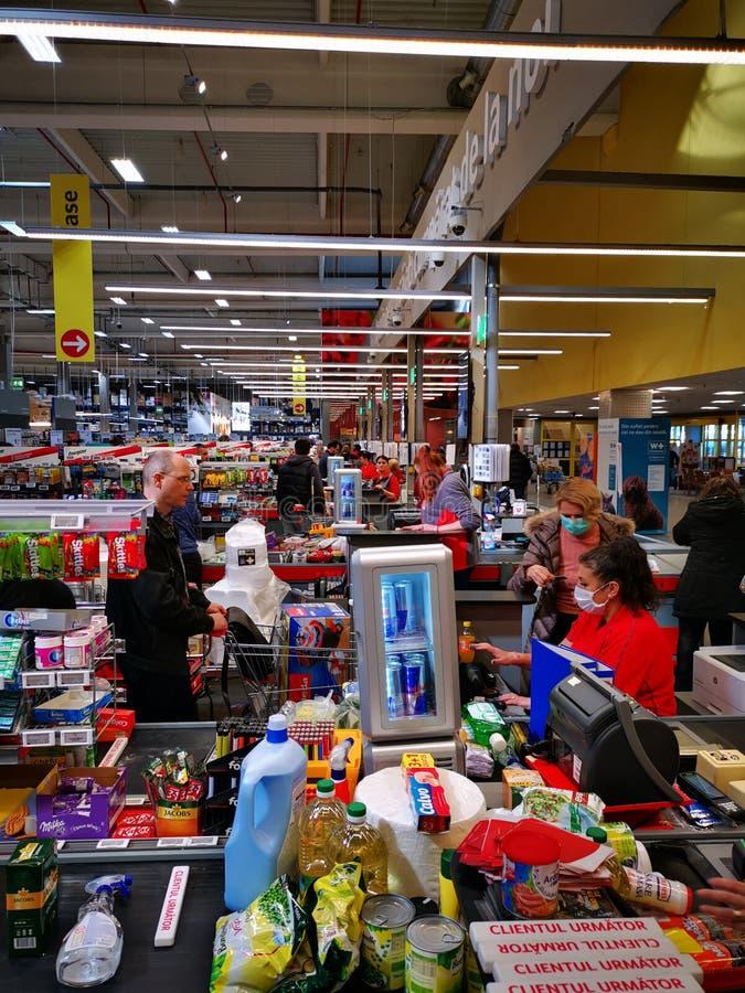 Comprar en la cinta en la caja registradora del supermercado foto de archivo libre de regalías