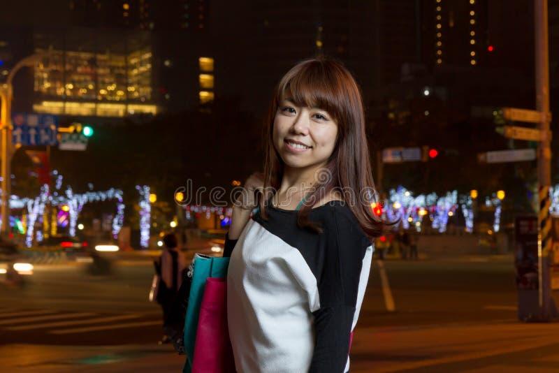 Compras asiáticas atractivas de la mujer en ciudad imagenes de archivo