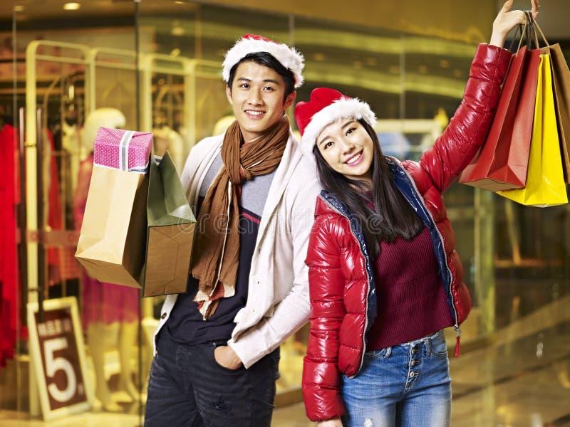 Compras asiáticas jovenes de los pares para la Navidad fotografía de archivo libre de regalías
