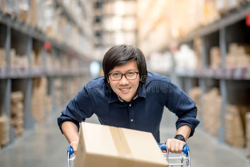 Compras asiáticas jovenes del hombre con el carro de la carretilla en almacén fotografía de archivo