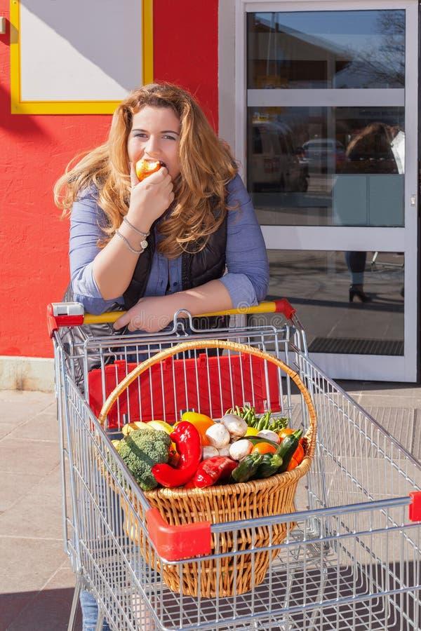 Compras atractivas de la mujer en la comida y probadas igualmente una manzana foto de archivo libre de regalías