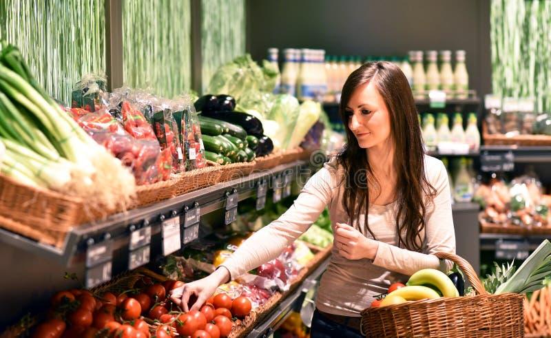Compras bonitas jovenes de la mujer para la comida sana fresca en el superm imagen de archivo