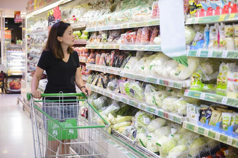 Compras chinas jovenes de la mujer en el supermercado foto de archivo libre de regalías