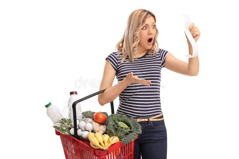 Compras chocadas de la mujer y mirada de la cuenta foto de archivo