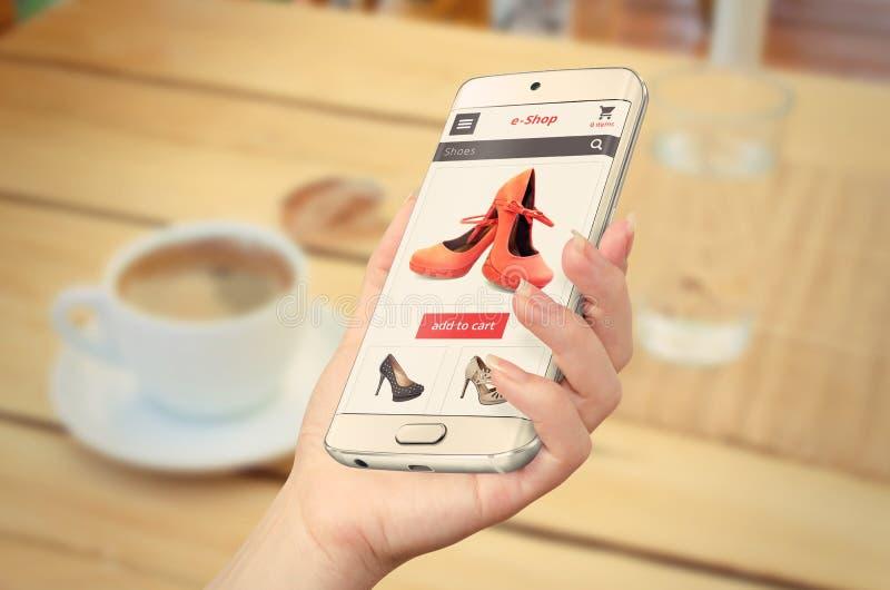 Compras de E con el teléfono elegante en mano de la mujer foto de archivo
