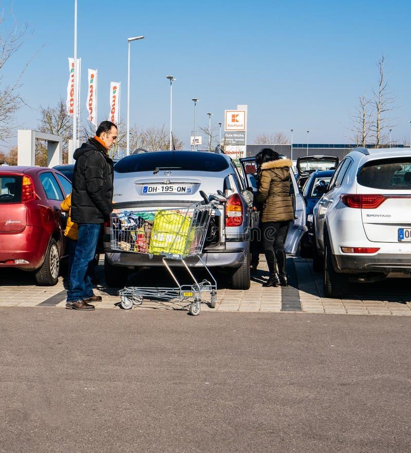 Compras de la familia para la comida en el estacionamiento del supermercado de Kaufland imagen de archivo libre de regalías