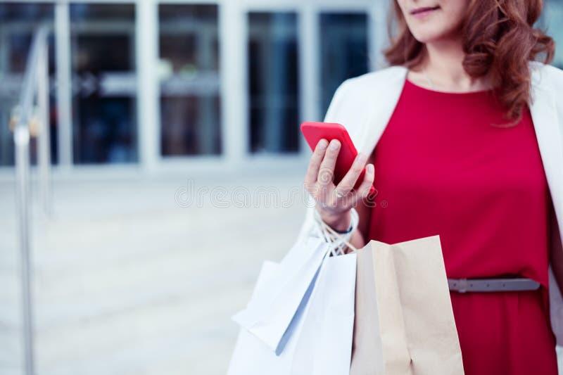 Compras de la mano de la mujer del comprador con un teléfono elegante y bolsos que llevan fotos de archivo