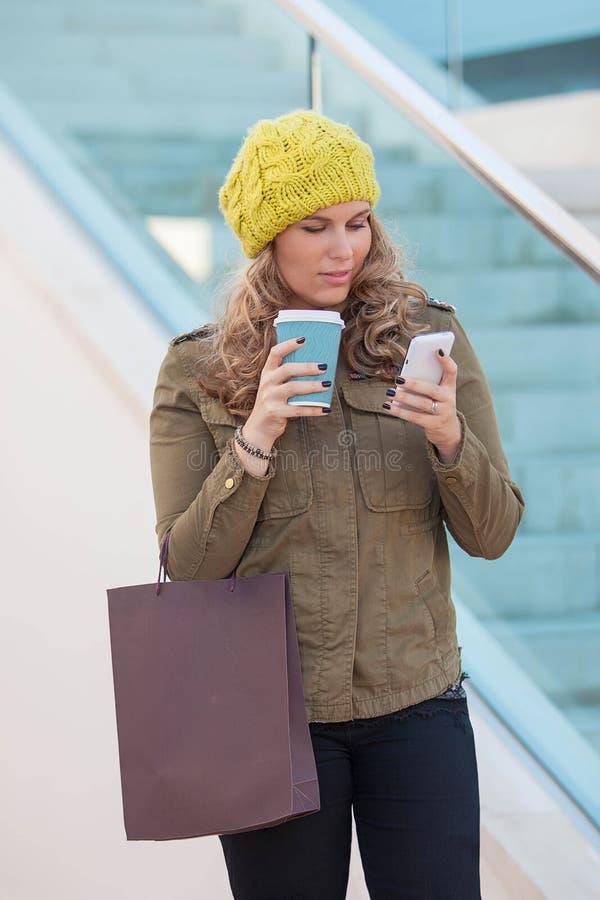 Compras de la mujer con café y el teléfono imagenes de archivo