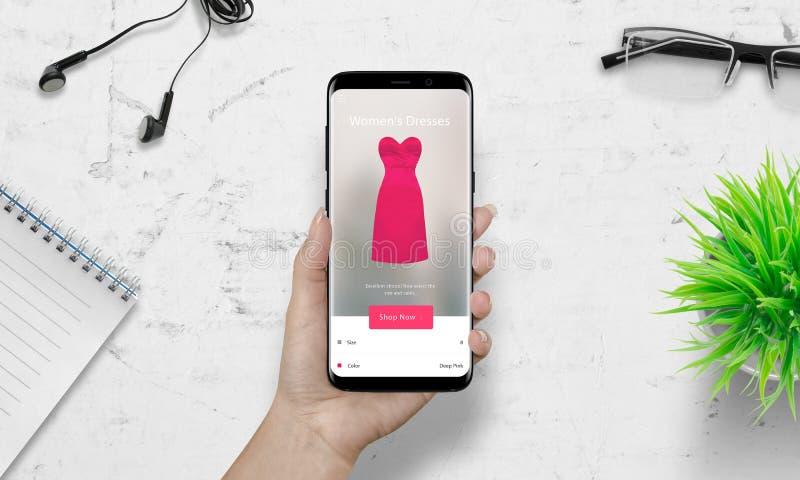Compras de la mujer con el teléfono elegante Vestido rosado de la mujer en el comercio electrónico app imágenes de archivo libres de regalías