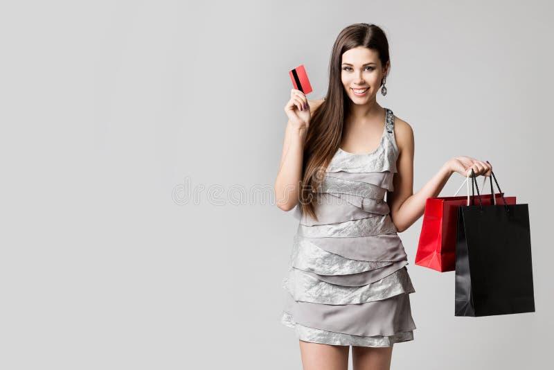 Compras de la mujer con la tarjeta de crédito y los bolsos, modelo de moda hermoso Studio Portrait, ropa de compra de la muchacha imágenes de archivo libres de regalías