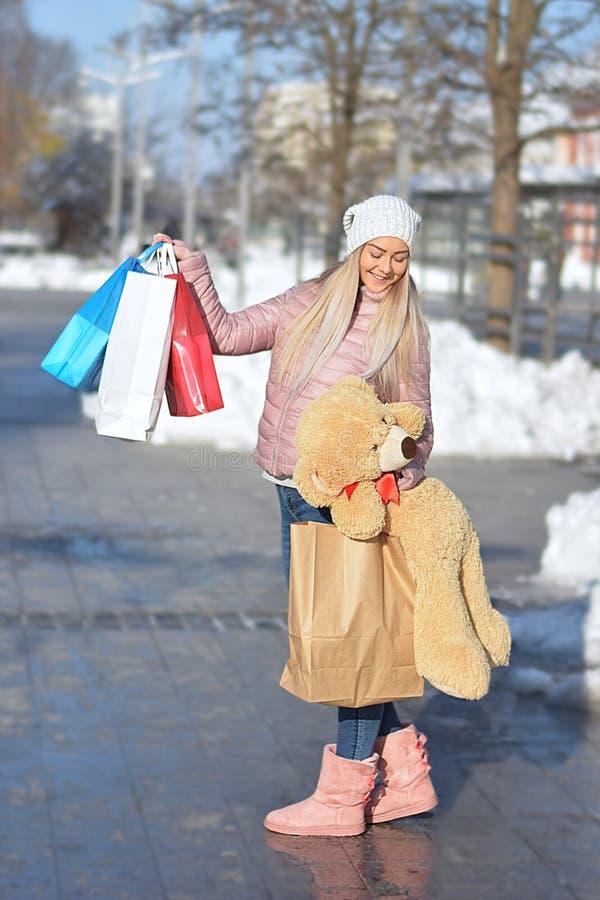 Compras de la mujer del comprador en la calle en invierno imágenes de archivo libres de regalías
