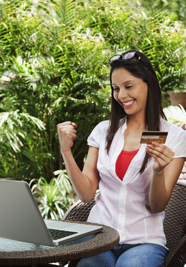 Compras de la mujer en línea y que hacen un puño fotografía de archivo libre de regalías