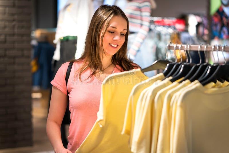 Compras de la mujer en tienda de la moda durante venta y liquidación imágenes de archivo libres de regalías
