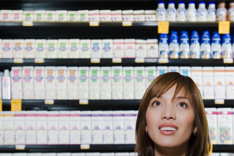 Compras de la mujer joven en un supermercado fotografía de archivo libre de regalías