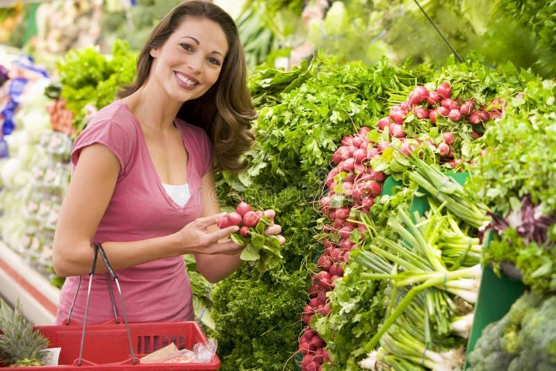 Compras de la mujer para el producto en supermercado fotografía de archivo libre de regalías