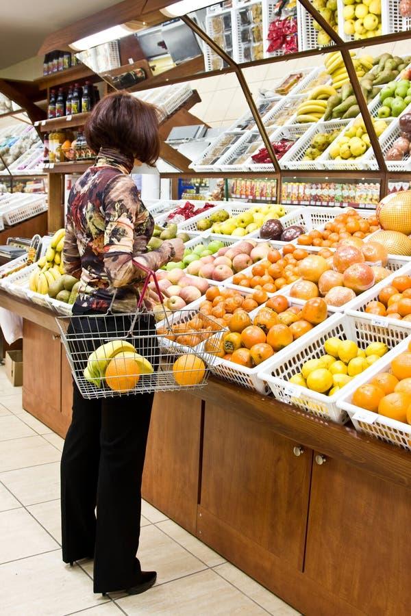 Compras de la mujer para las frutas foto de archivo libre de regalías