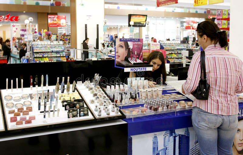 Compras de la mujer para los cosméticos en el supermercado fotos de archivo