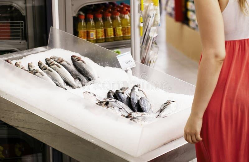 Compras de la mujer para los pescados en un supermercado imágenes de archivo libres de regalías