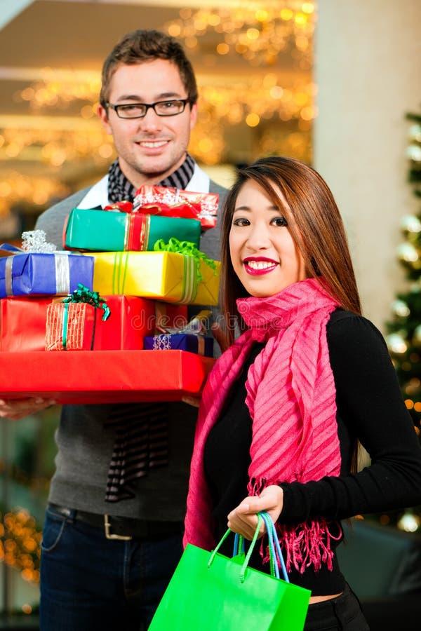 Compras de la Navidad de los pares con los presentes en alameda imagen de archivo