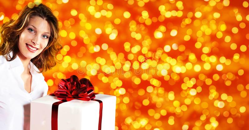 Compras de la Navidad, mujer con el paquete del regalo en el li brillante borroso fotos de archivo