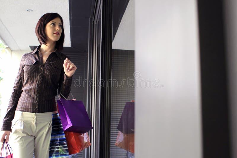 Compras de la ventana de la mujer joven imagen de archivo libre de regalías