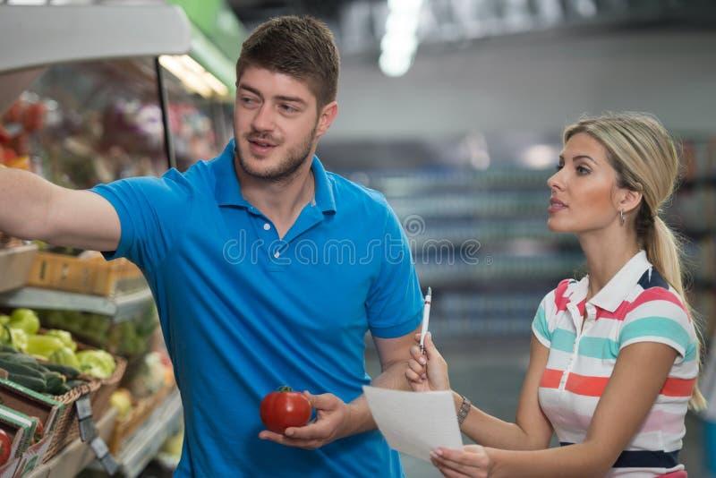 Compras de los pares en el supermercado con la lista del ultramarinos imagenes de archivo